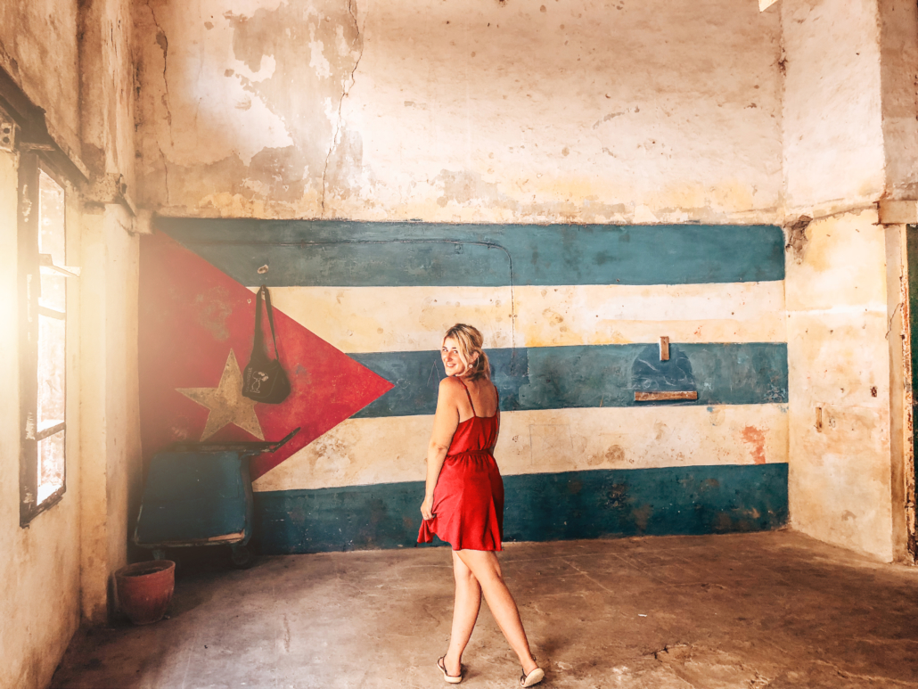 Women in red dress standing in front of the Cuban Flag Mural in an abandoned building