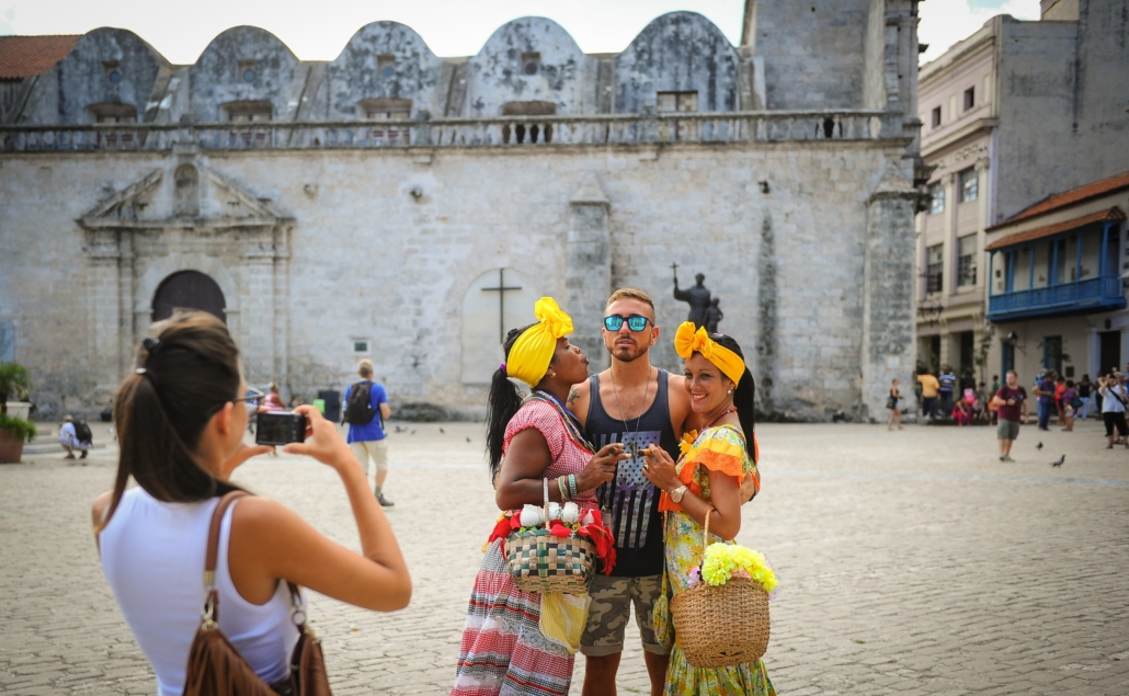 Things to know Cuba: Tourist man posing with women in traditional wear while woman takes a picture in the plaza