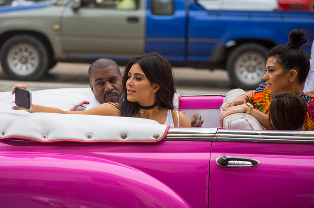 Kardashians in classic car convertible, pink, taking a selfie